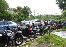 Bikes and cars lined up along the road